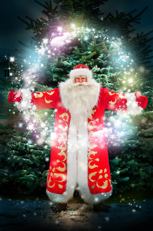 conjuring: Portrait of Santa Claus conjuring against christmas tree