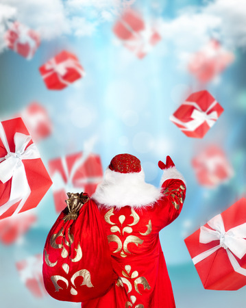 Santa Claus standing and doing magic. Gift boxes falling down around him photo