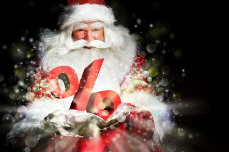 Santa Claus holding his bag and smiling. Lights and sparks are flying from the bag. Diccount symbol sign in front of Santa photo