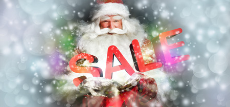 Santa Claus holding his bag and smiling. Lights and sparks are flying from the bag. Sale sign in front of Santa photo