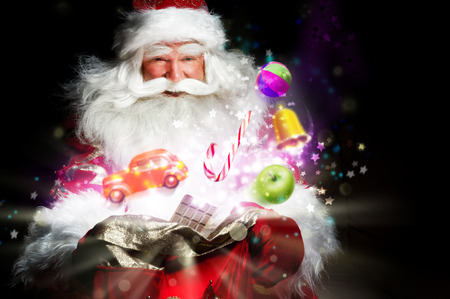 christmas santa: Santa Claus getting gifts and confection from his bag and showing miracle Stock Photo