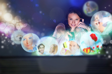 hdtv: Young woman watching tv at home. Holding remote control and choosing channel.