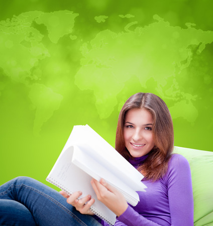 beanbag: Young adult woman writing in her copybook while sitting on a large beanbag against world map