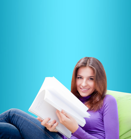 beanbag: Young adult woman writing in her copybook while sitting on a large beanbag against blue background