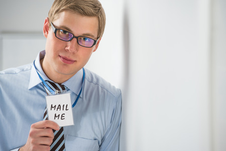 Handsome businessman showing 'mail me' text on a badge photo