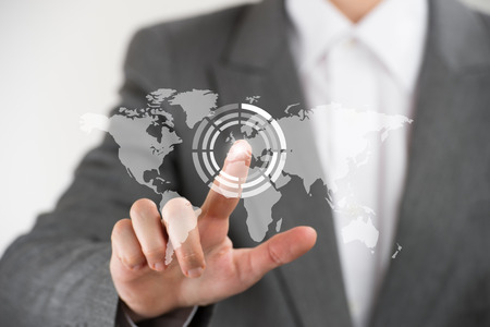 Business woman pointing her finger on virtual button on world map photo