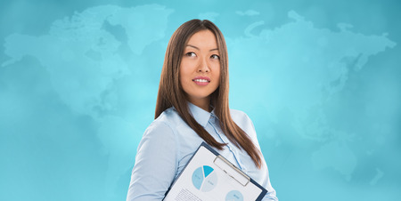 Asian business woman holding reports and smiling against world map background. Copy space photo