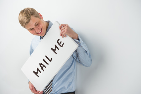 Handsome businessman showing 'mail me' text on a billboard photo
