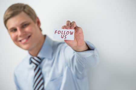 Handsome businessman showing follow us text on a business card photo