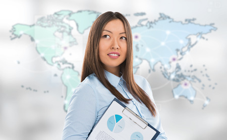 Asian business woman holding reports and smiling against world map background. Copyspace photo