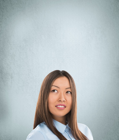 Portrait of happy Caucasian business woman standing over grunge background photo