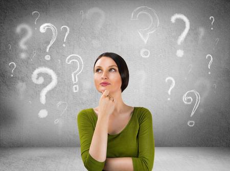 questionnement: Belle femme avec questionnement expression et des points d'interrogation au-dessus de sa t�te Banque d'images