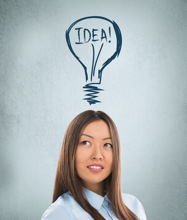Idea woman - brainstorming. Beautiful young businesswoman contemplating. Graphic lamp - symbol of new idea, overhead photo