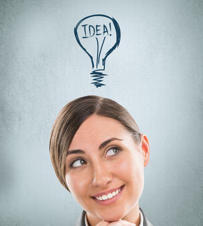 Mujer Idea - lluvia de ideas. Hermosa joven empresaria contemplando. L�mpara Gr�fico - s�mbolo de la nueva idea, los gastos generales