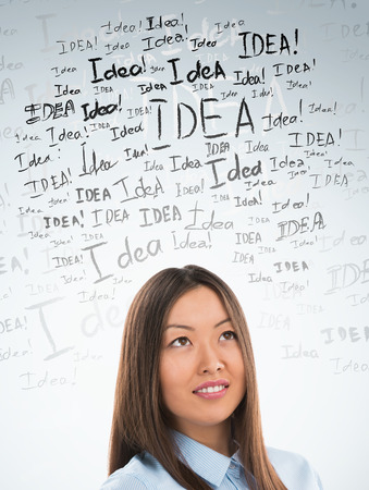 creative thinking: Idea concept. Young business woman with idea signs in front