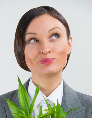 Adult business woman looking up and holding lucky bamboo plant symbol of success. Business growing concept photo