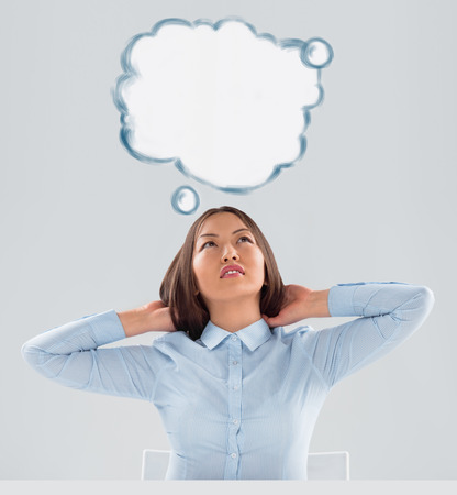 Image of young woman thinking of her plans. Lots of copyspace inside graphic cloud for your text photo