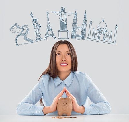 Young pretty business woman dreaming about vacation and saving money with piggy bank for her trip to famous touristic destination. Architecture symbols overhead photo