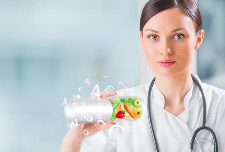 Concepto de vida sana. Mujer m�dico de la celebraci�n de las vitaminas Foto de archivo