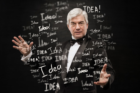 mature business man: Idea concept. Mature business man standing on black background with idea signs in front Stock Photo
