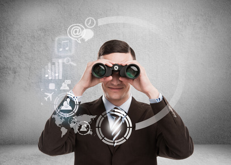 Technology concept. Businessman with biboculars and virtual interface with web and social media icons photo