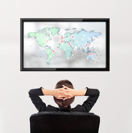 Woman watching tv. Photo from behind. Worldmap at the screen photo