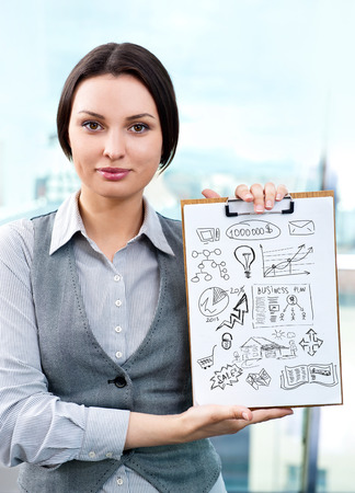 Business woman holding papers with sketches for her business photo