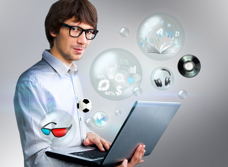 Handsome man holding laptop. Different objects are flying from the screen photo