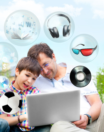 Closeup portrait of happy family: father and his son using laptop outdoor at their backyard sitting on the grass together. Different objects flying from the screen photo
