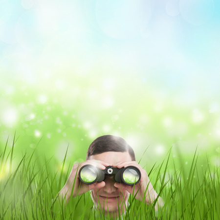Man looking through binoculars from grass. Lots of copyspace. Head hunting or looking for something concept. photo
