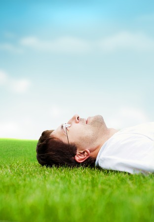 Young good looking man in white shirt lying on grass and looking at the sky photo