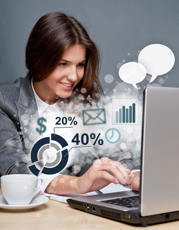 working woman: Young business woman working on her laptop. Different icons with functional symbols are flying out of the screen