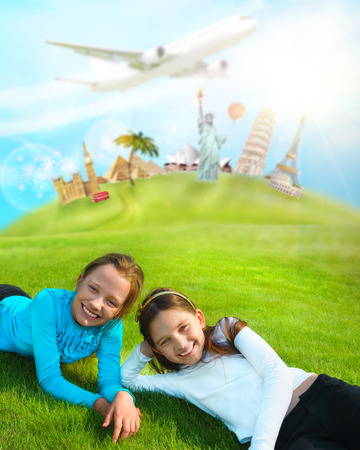 Two young girls laying on a grass against worlds famous buildings. Educational traveling concept photo