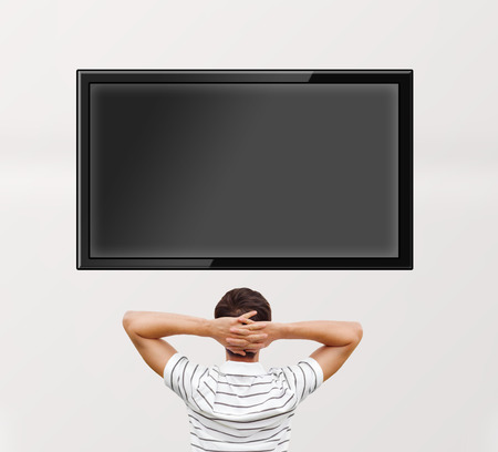 Man watching tv. Photo from behind. Editable copyspace at the screen