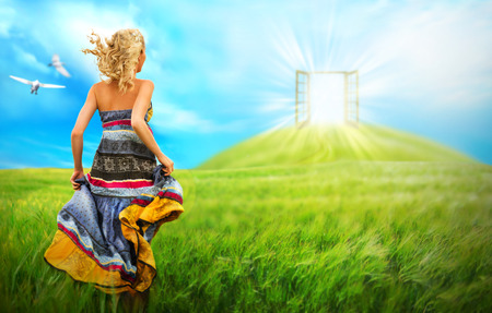 Young woman running across beautiful field to the bright luminous door on a hill. Bright future affection concept