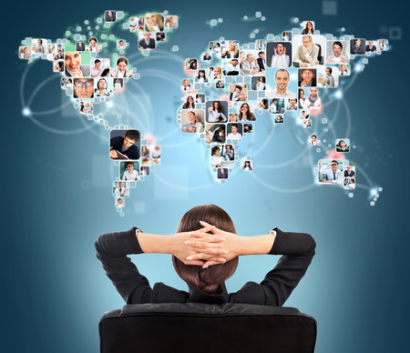 connect: Portrait of young woman communicating with her friends across the world. Sitting against world map with photo of people. International communications concept