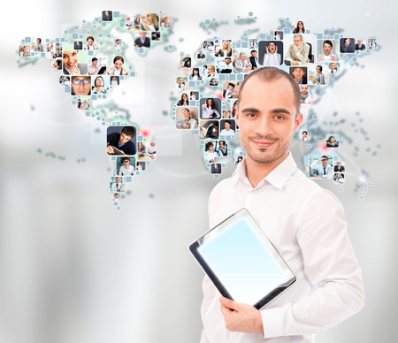 chat online: Portrait of adult man communicating with his friends across the world. Standing against world map with photo of people. International communications concept