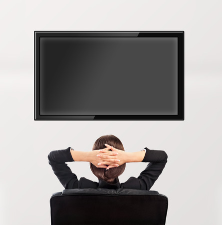 tv panel: Woman watching tv. Photo from behind. Editable copyspace at the screen Stock Photo