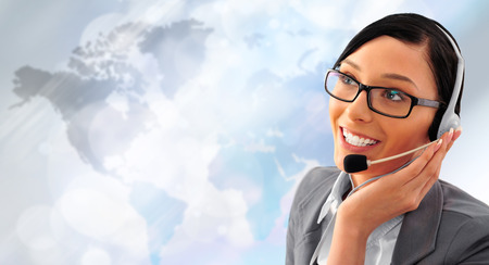 hands free device: Telemarketing headset woman from call center smiling happy talking in hands free headset device. Business woman in suit in front of world map background. Stock Photo