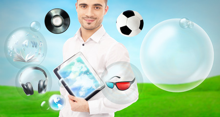 Adult handsome man holding tablet computer. Icons of different object are flying around. All multimedia in one mobile gadget concept photo