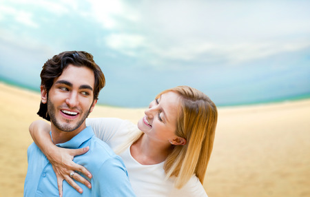 idealistic: Portrait of young couple in love embracing at beach and enjoying time being together. Idealistic artistic photo poster for advertisement banner