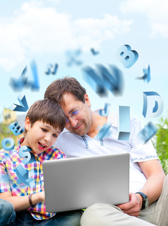 Closeup portrait of happy family: father and his son educating using laptop outdoor at their backyard sitting on the grass together Stock Photo