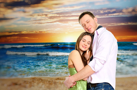 Portrait of young couple in love embracing at beach and enjoying time being together