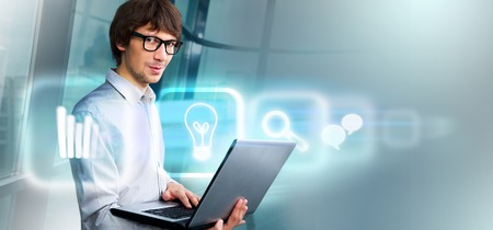 Business man holding laptop and working with virtual interface. Merge of technologies concept