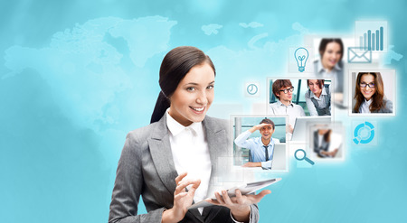 chat online: Portrait of businesswoman holding her tablet computer and communicating with her team across the world. International communications concept