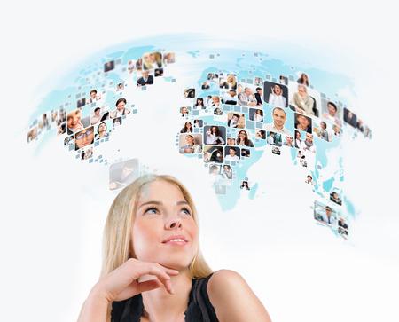 Jonge vrouw op zoek naar virtuele wereldkaart met foto van verschillende mensen over de hele wereld. Internationale communicatie of online community concept.