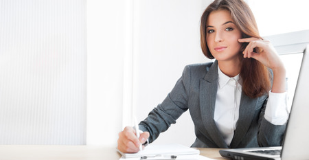 Mujer de negocios hermosa joven que se sienta relajado en su oficina y mirando a la c�mara