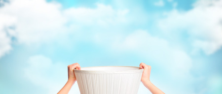 Female hands holding empty basket against beautiful sky