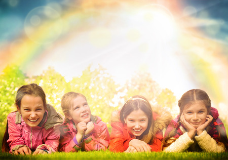 Happy group of girls lying on a green grass. Rainbow and sun overhead photo