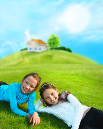 Two young girls laying down on grass and smiling. Beautiful house and tree on hill photo